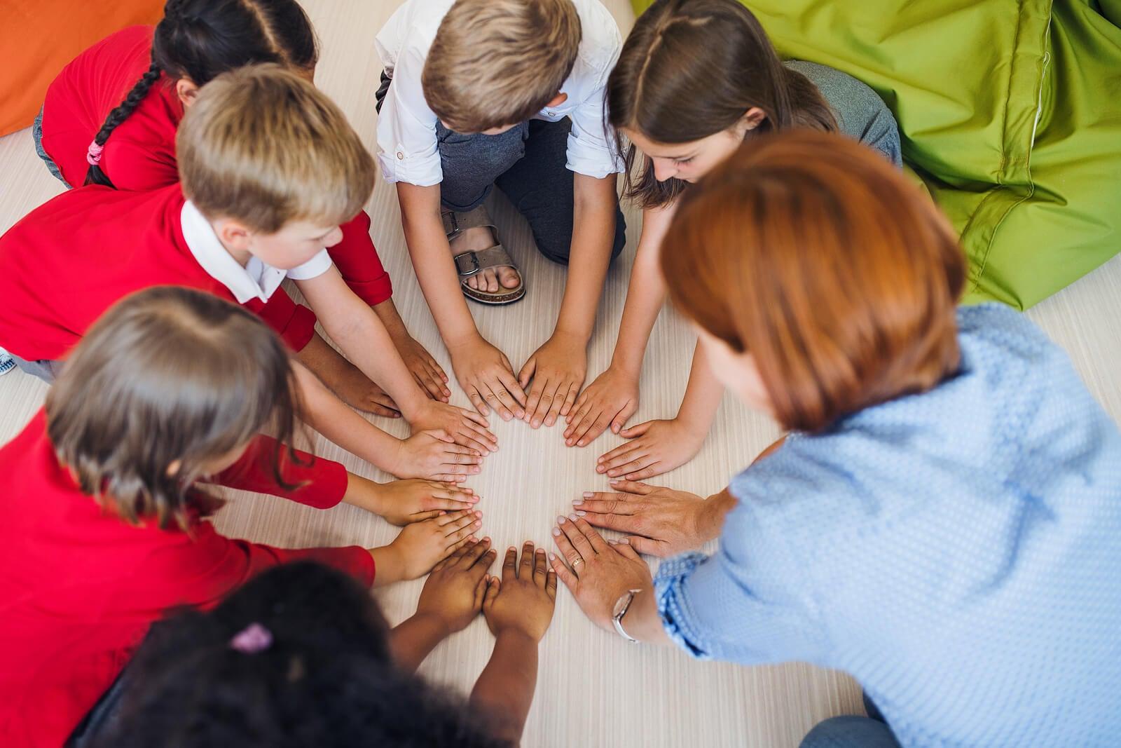 Profesora con sus alumnos haciendo el círculo mágico.