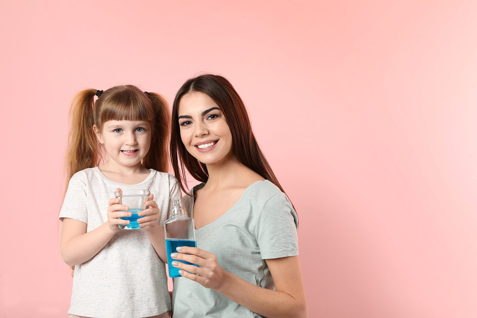 Madre e hija llevando a cabo una rutina de enjuague bucal para niños.