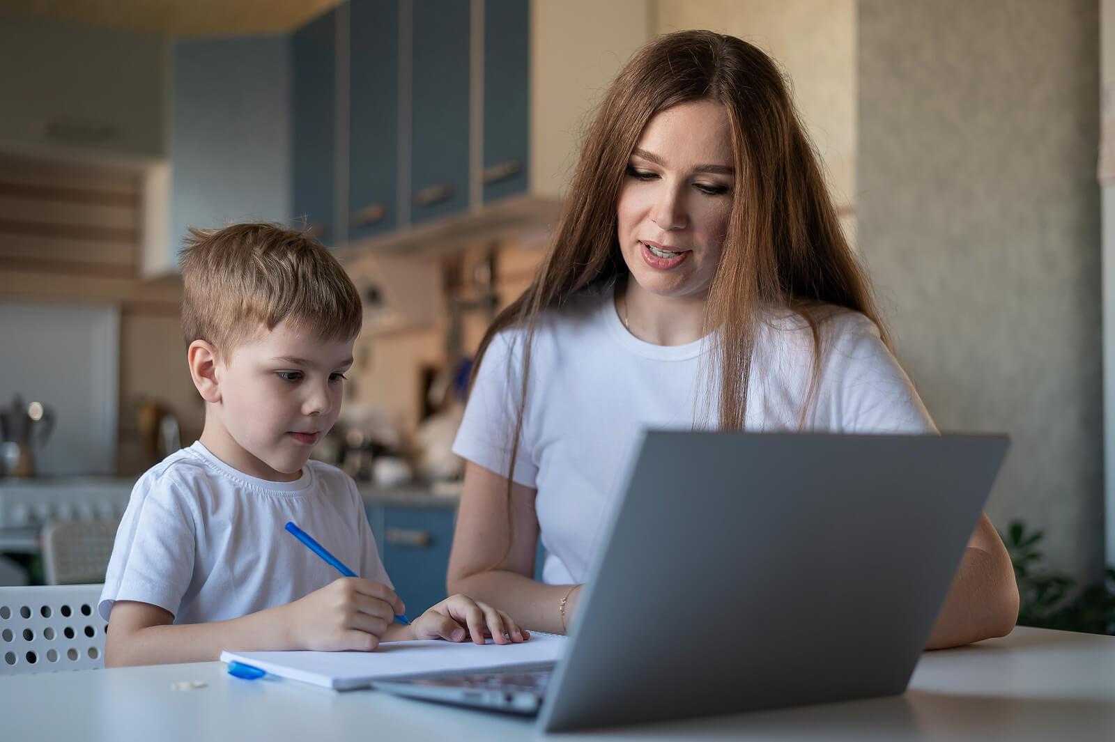 Madre con su hijo haciendo un dictado en casa.