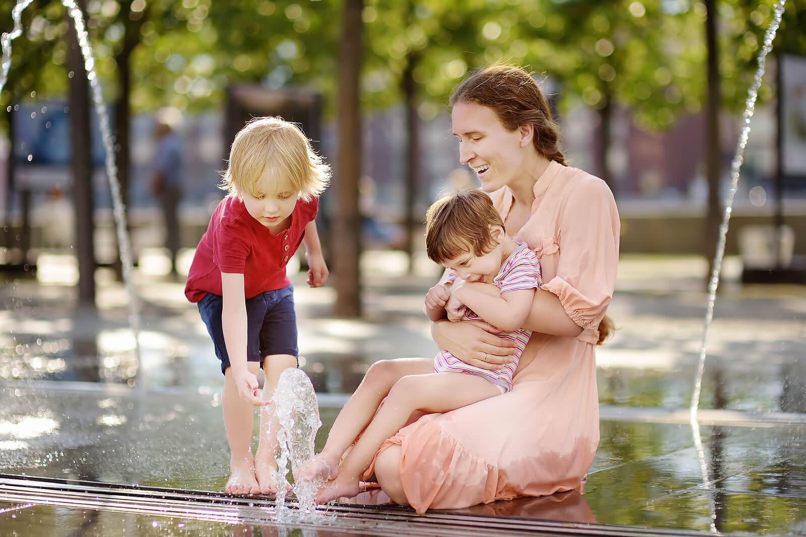 Madre jugando con sus hijos junto a una fuente.