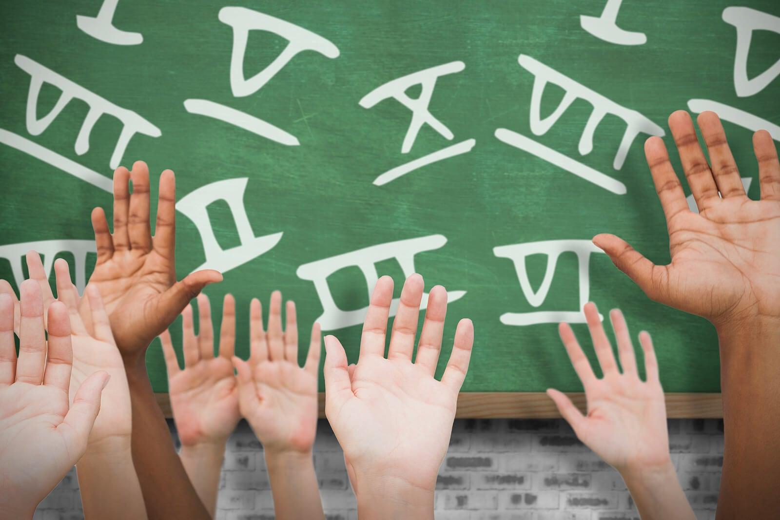 Alumnos con las manos levantadas para aprender los números romanos.