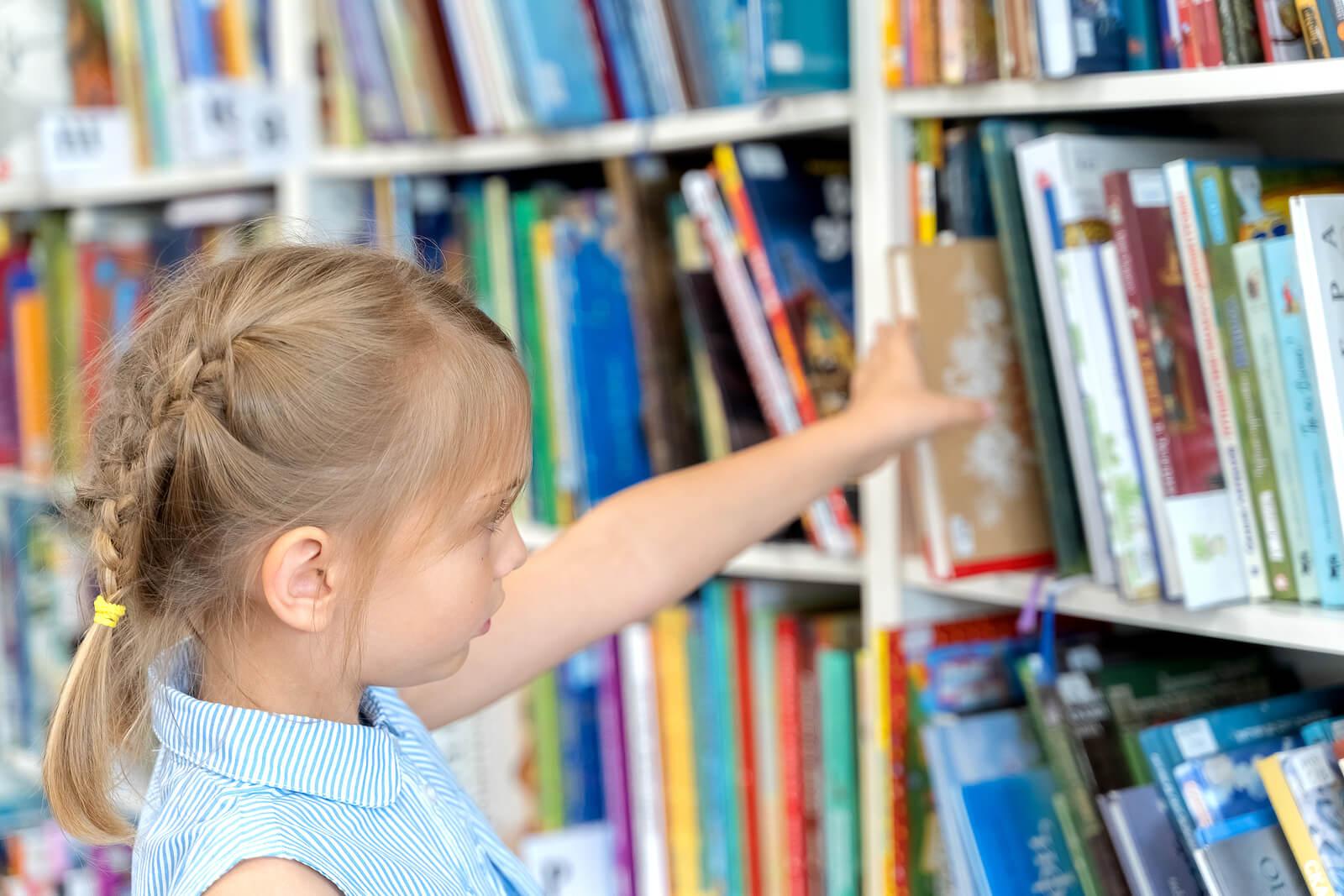Niña con altas capacidades cogiendo un libro de la biblioteca.