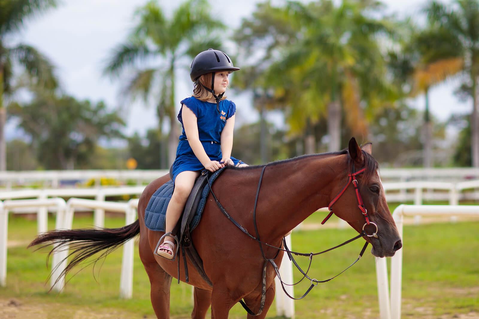 Niña montando a caballo porque la equitación es uno de los mejores deportes para niños con autismo.