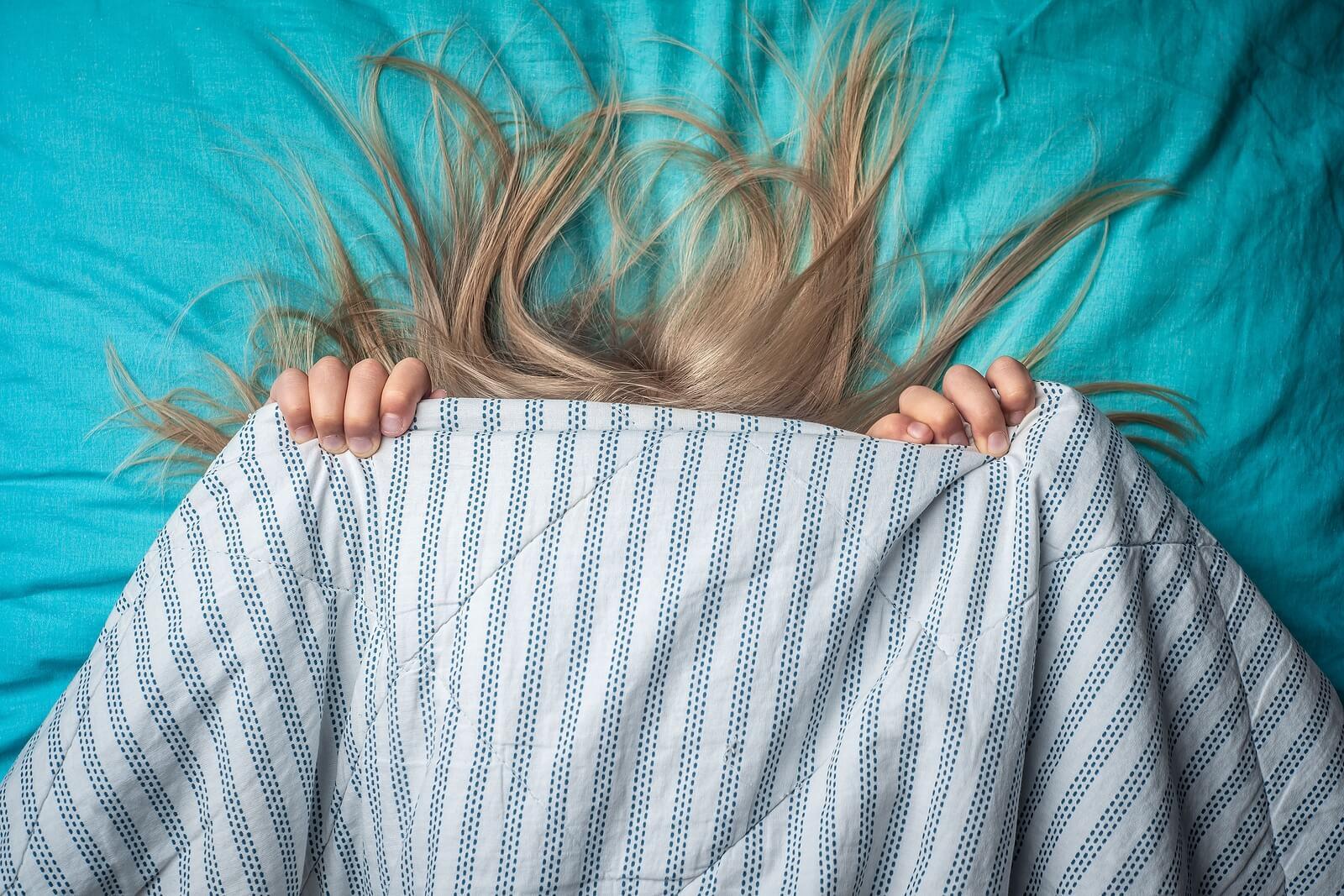 Une jeune fille qui se cache sous un drap.