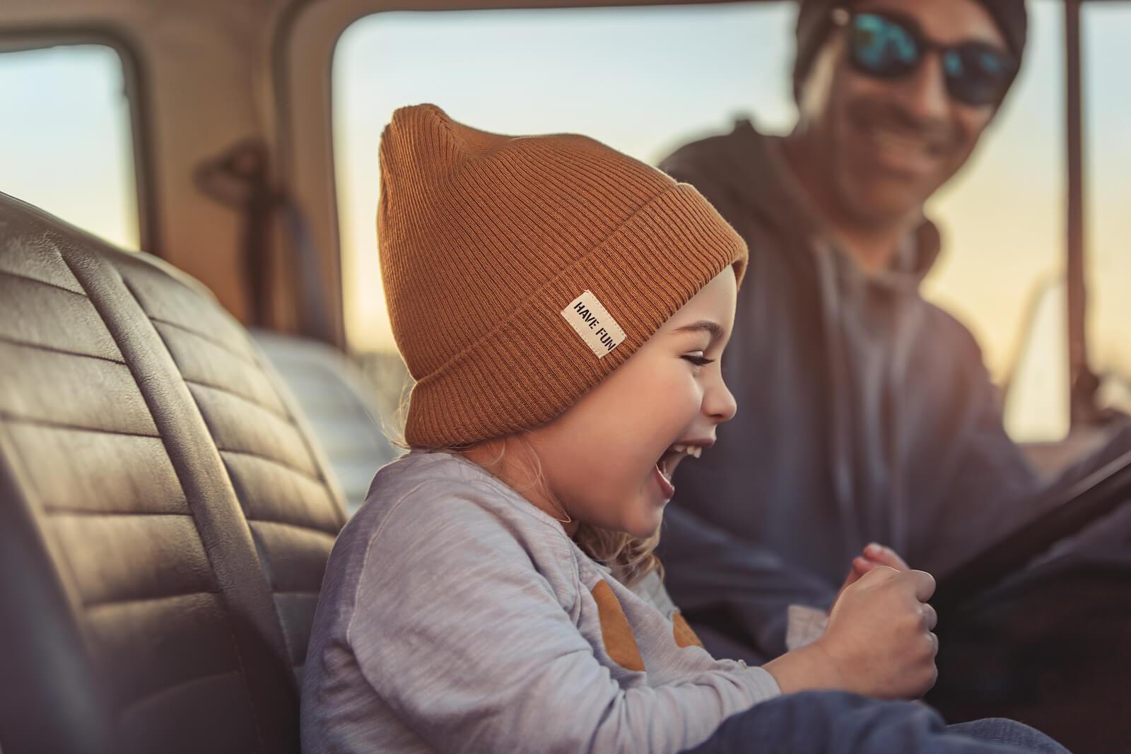 Niña riéndose con su padre en el coche.