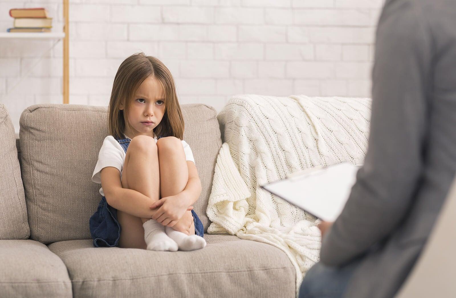 Niña enfadad sentada en el sofá porque su madre la ha regañado.