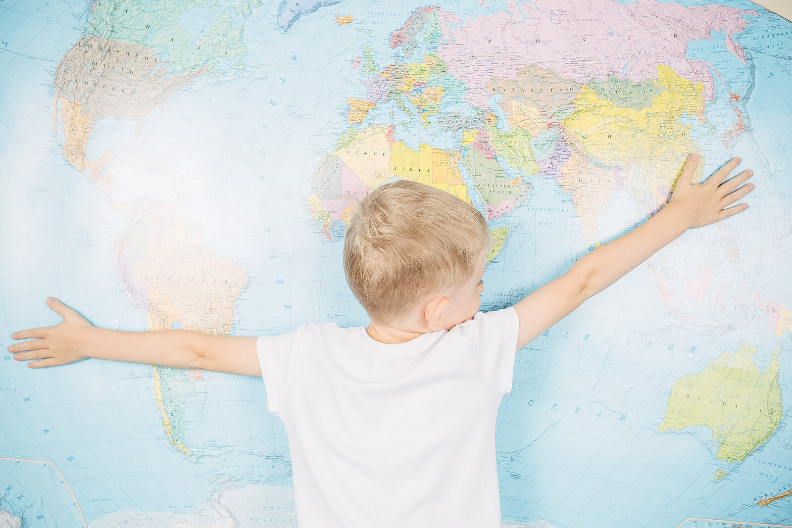 Niño abrazando un mapamundi infantil.