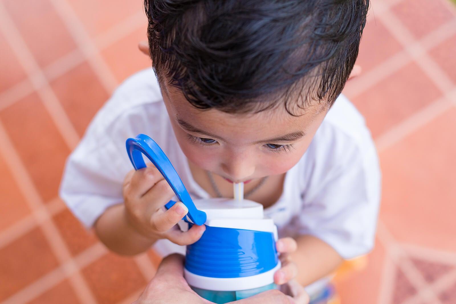 Niño bebiendo agua porque está sudando.