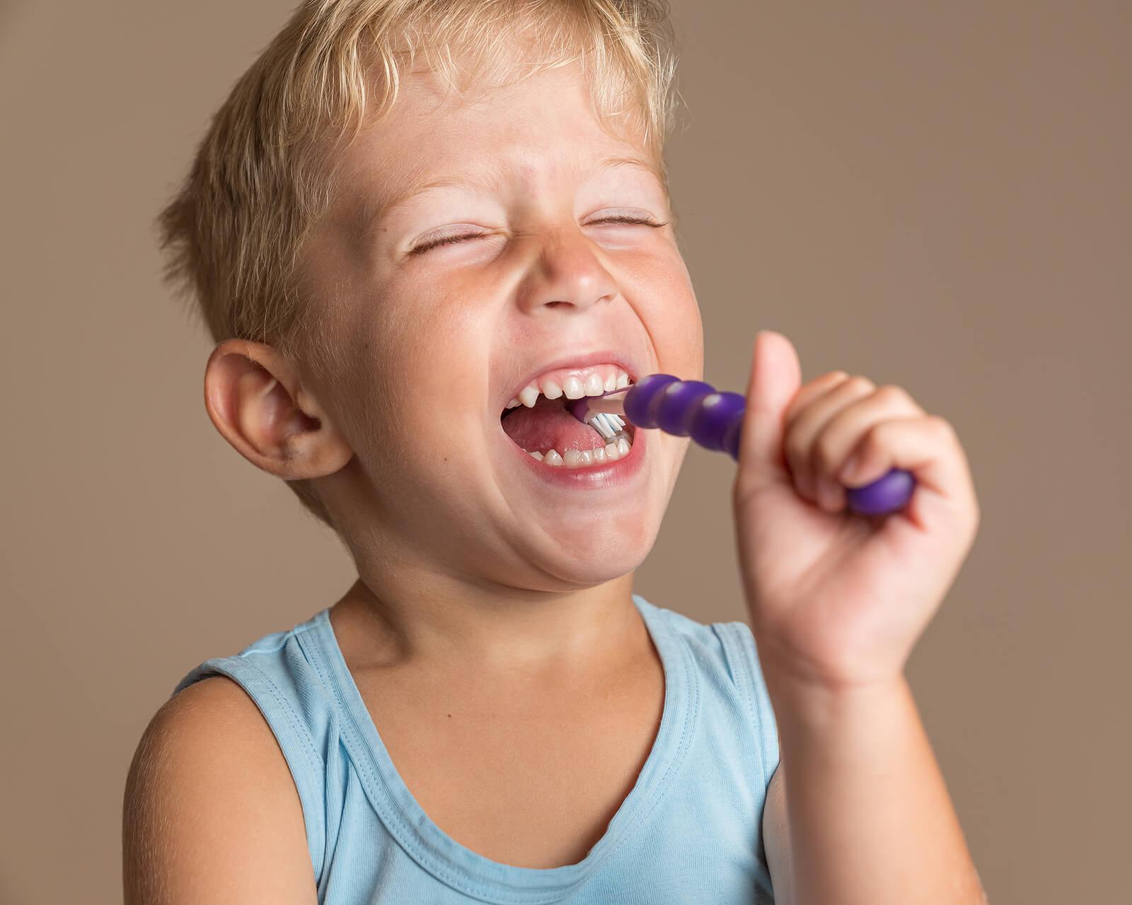 Niño cepillándose los dientes feliz con una pasta con flúor.