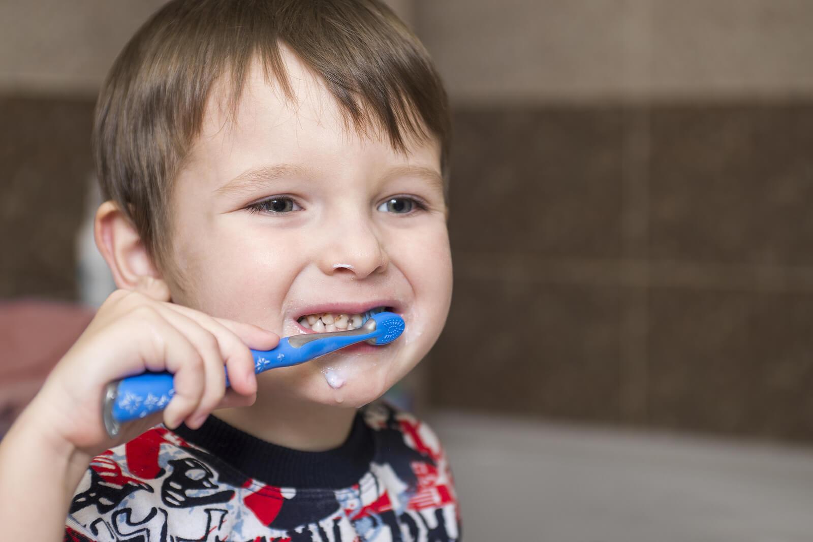 Niño cepillándose los dientes para evitar la sensibilidad dental en niños.