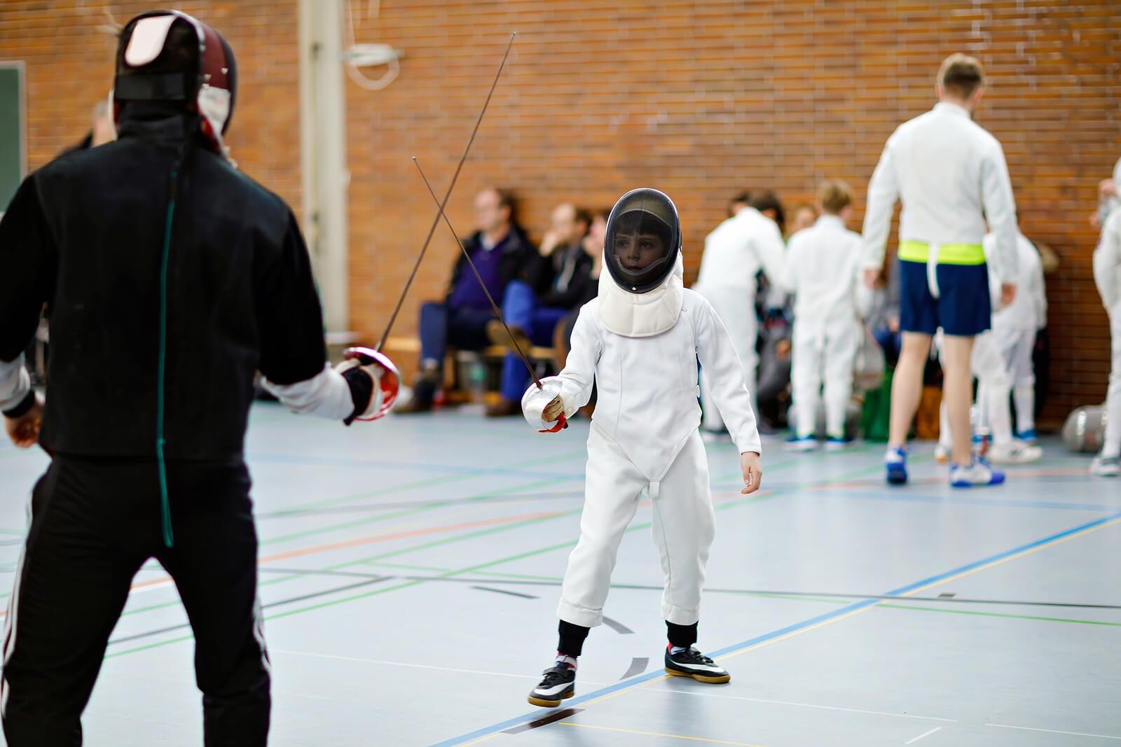 Niño en una competición de esgrima como deporte infantil.
