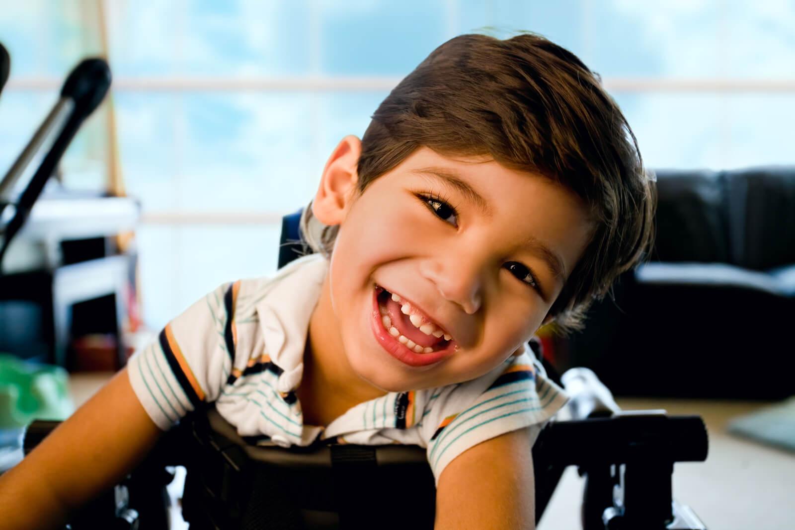 Niño con discapacidad muy sonriente y feliz.