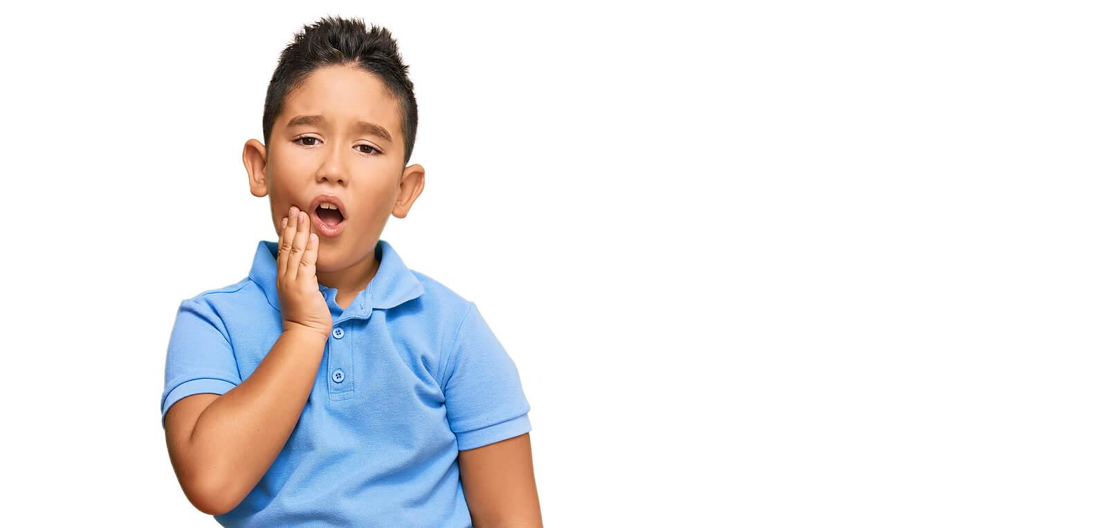 Niño con dolor de boca porque sufre sensibilidad dental.