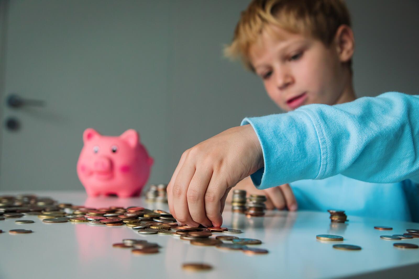 Niño aprendiendo a ahorrar el dinero que le dan de paga.