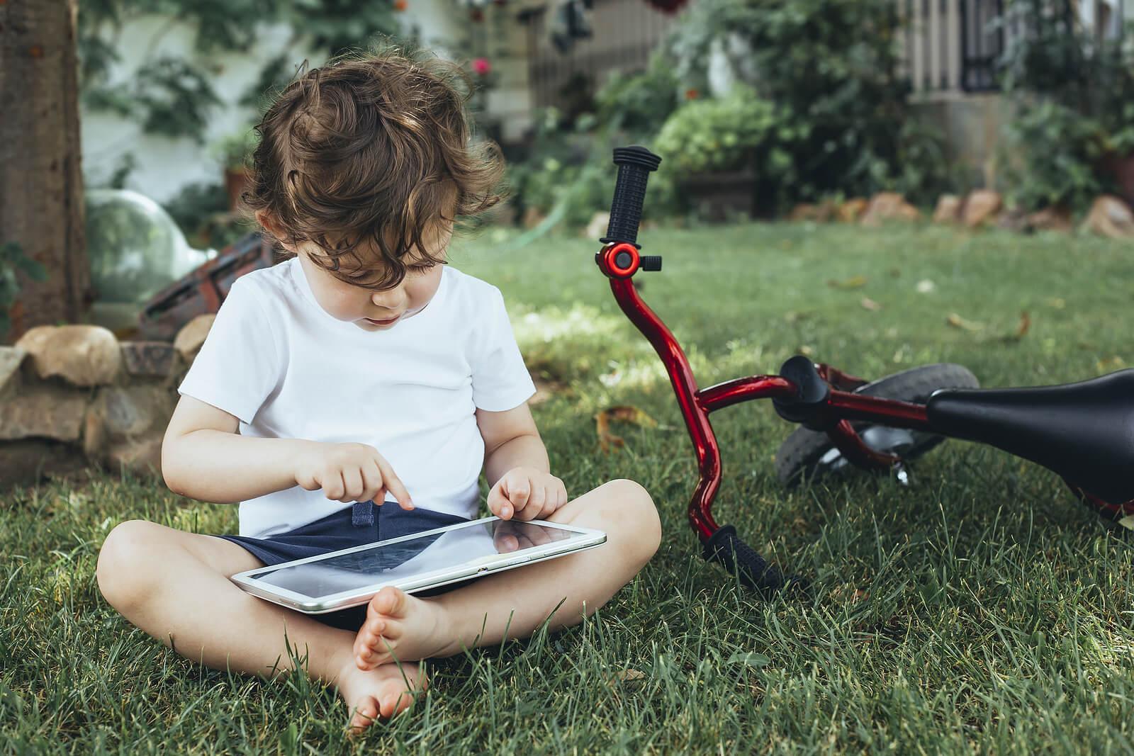 Niño jugando con una tablet junto a su bicicleta.