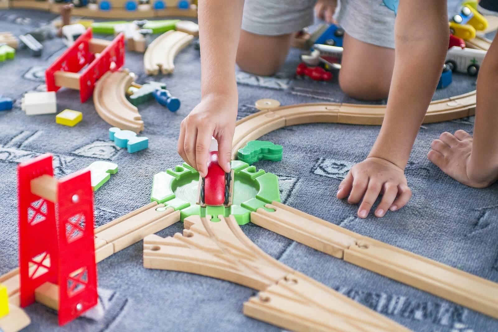 Niño jugando con trenes en su zona de juegos.