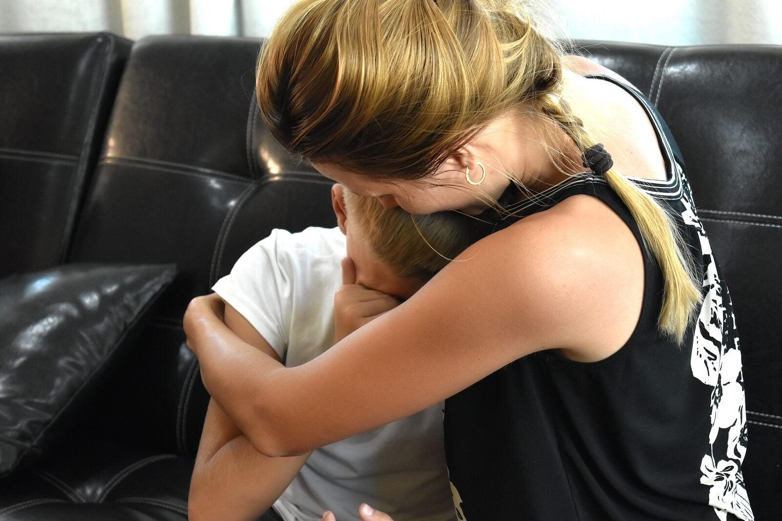 Madre abrazando a su hijo con asiedad infantil.