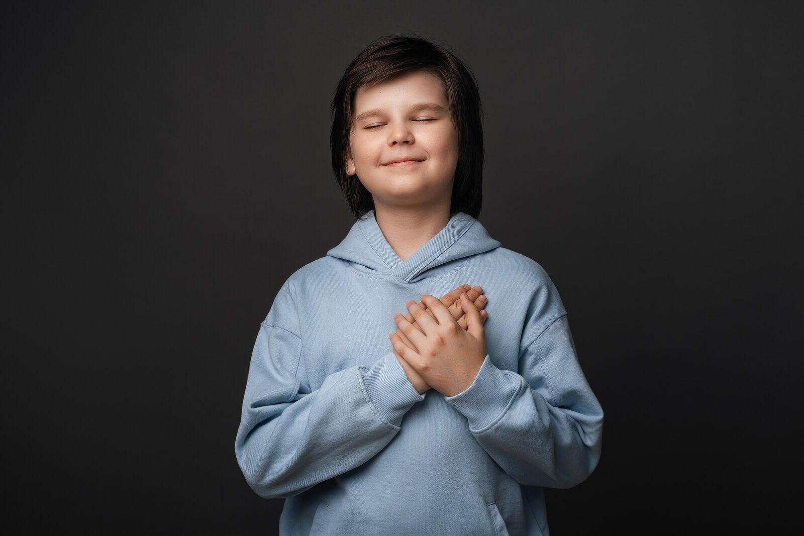 Niño con la mano en el corazón lleno de gratitud.