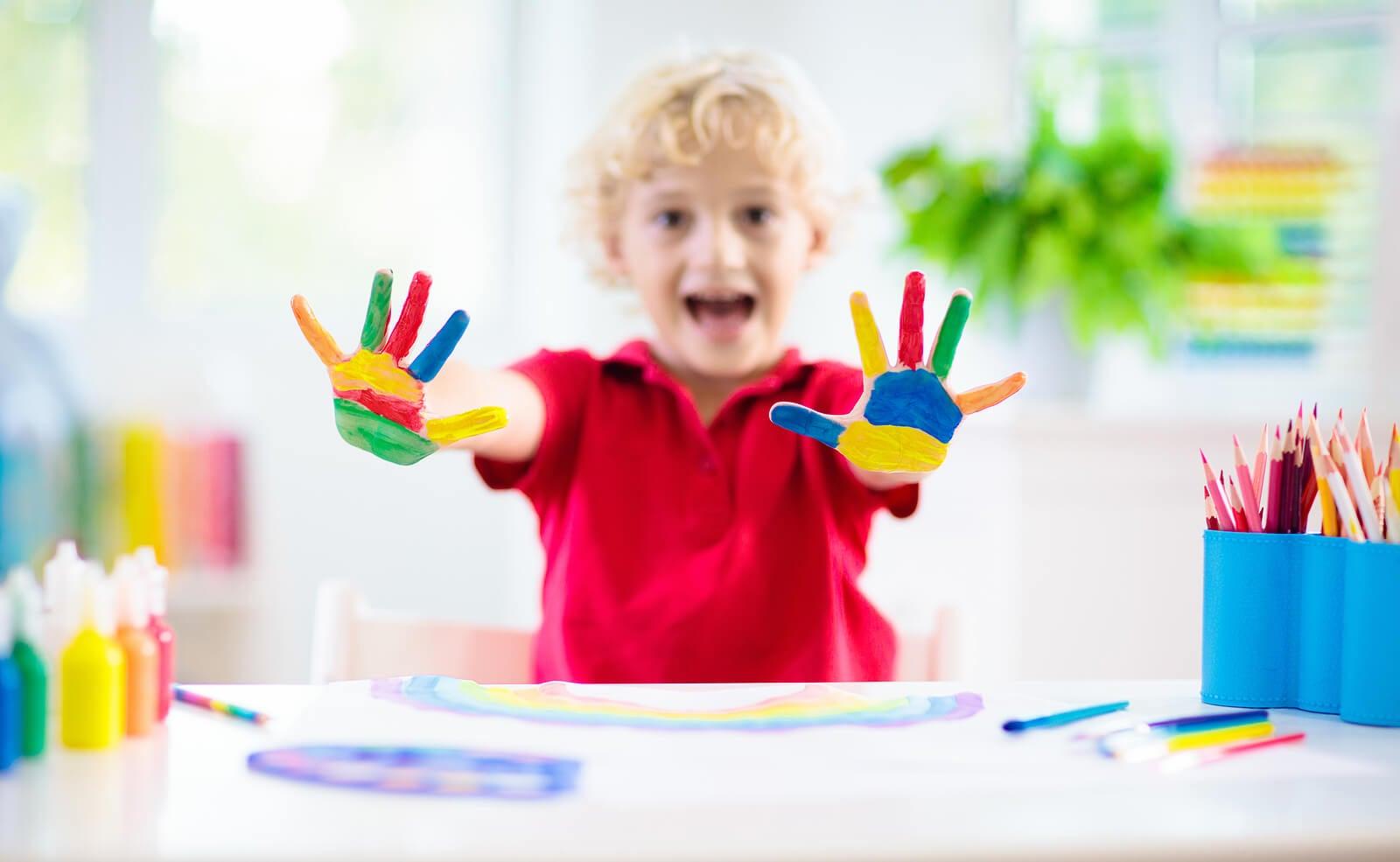 Niño jugando a pintar con los dedos.