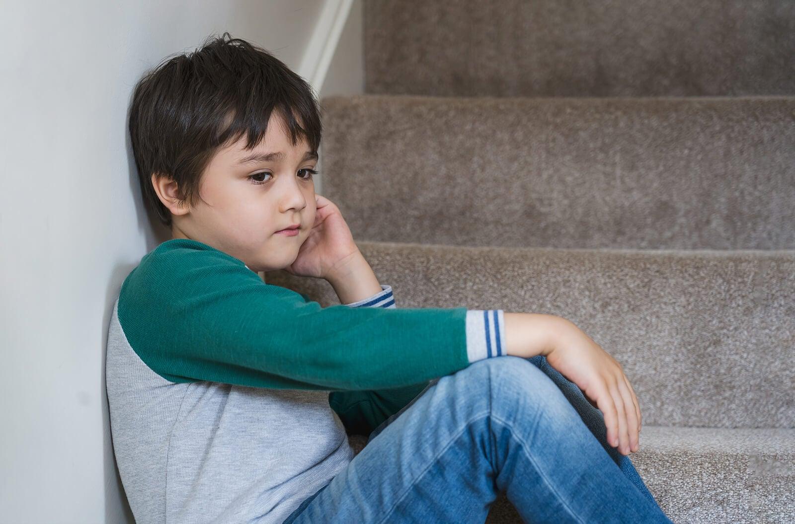Niño triste sentado en las escaleras.