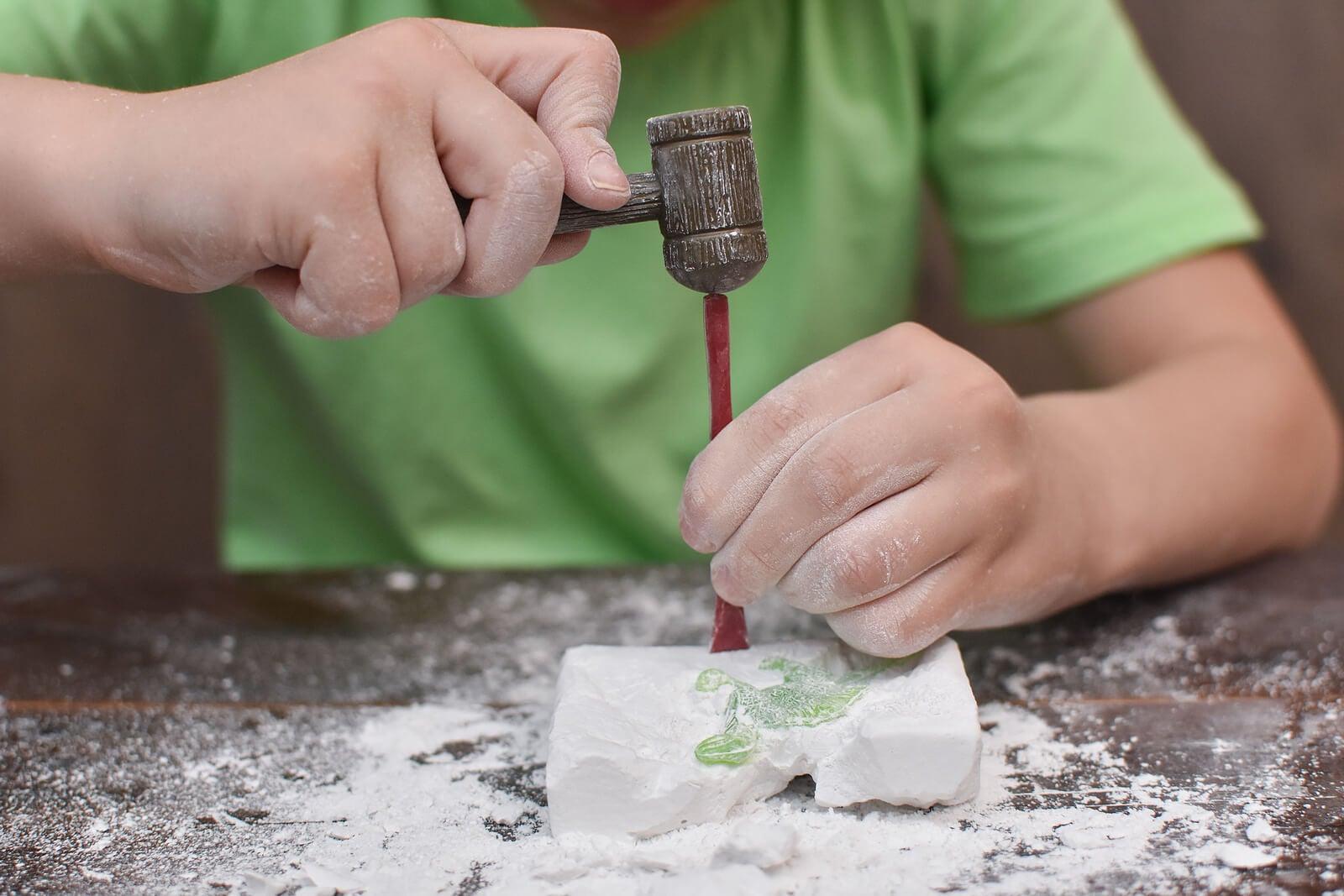 Niño haciendo un taller de geología con dinosaurios.
