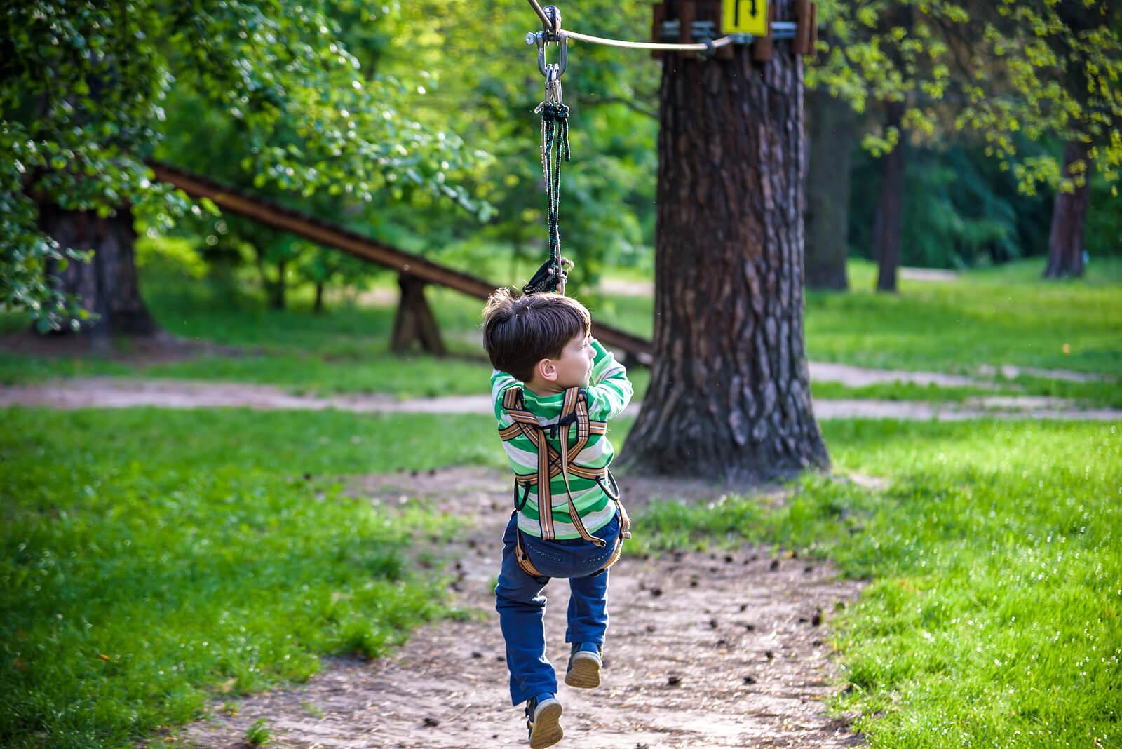 Niño lanzándose por una tirolina en el bosque.