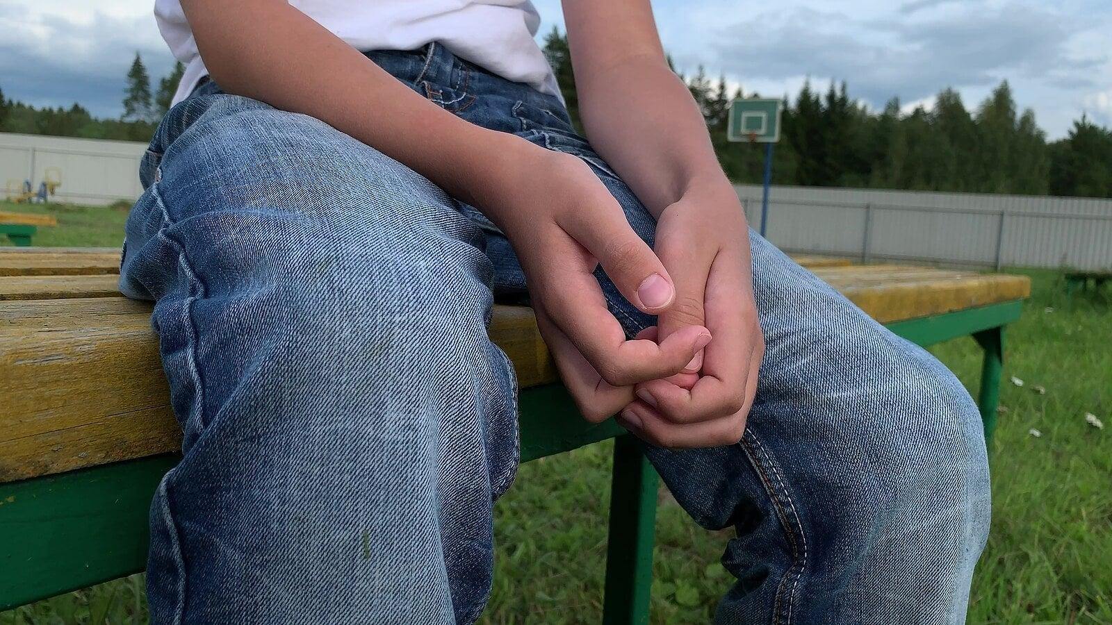 Niño sentado en un banco del parque solo con depresión infantil.