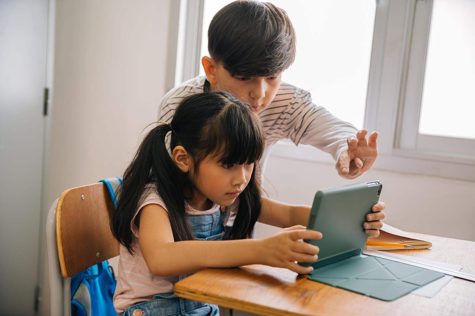 Niños nativos digitales consultando información en la tablet.