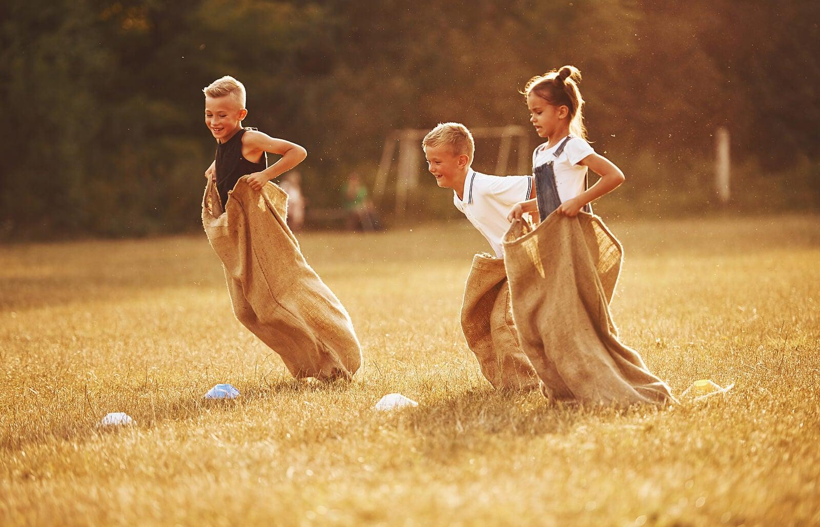 Niño haciendo una carrera de sacos, una de las actividades deportivas divertidas para niños.
