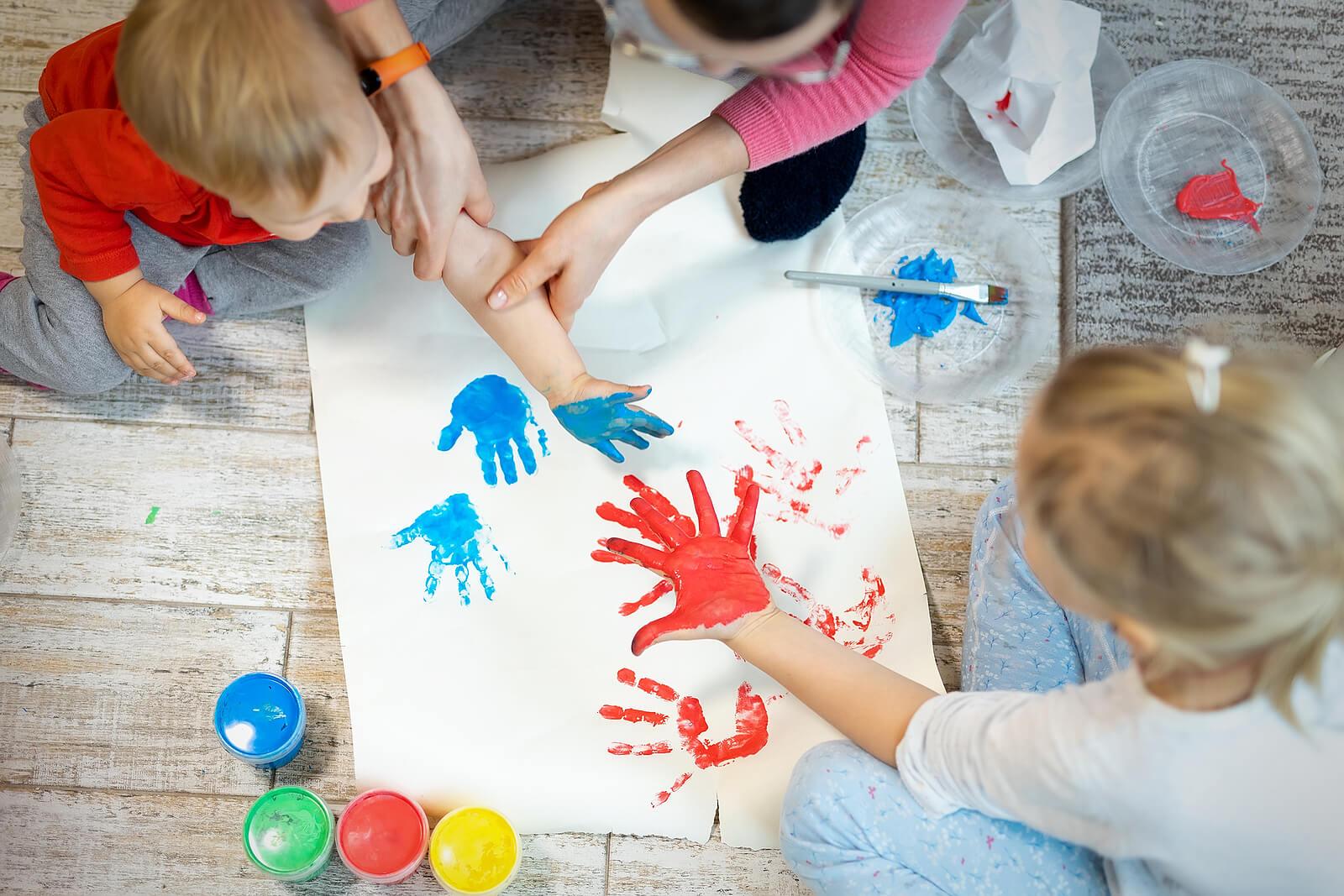 Madre con sus hijos jugando a pintar con los dedos y las manos un mural.