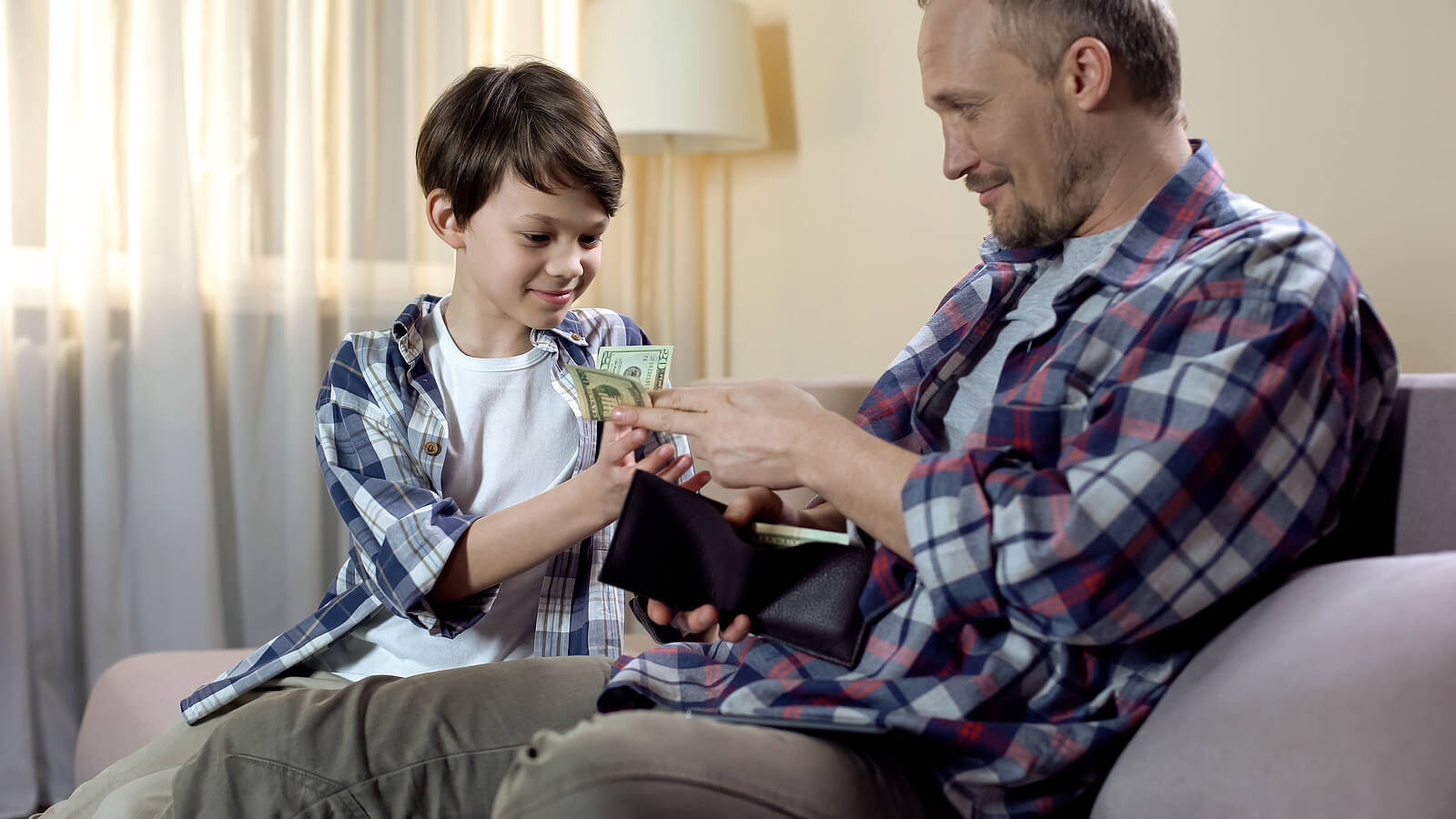 Padre dándole la paga a su hijo.