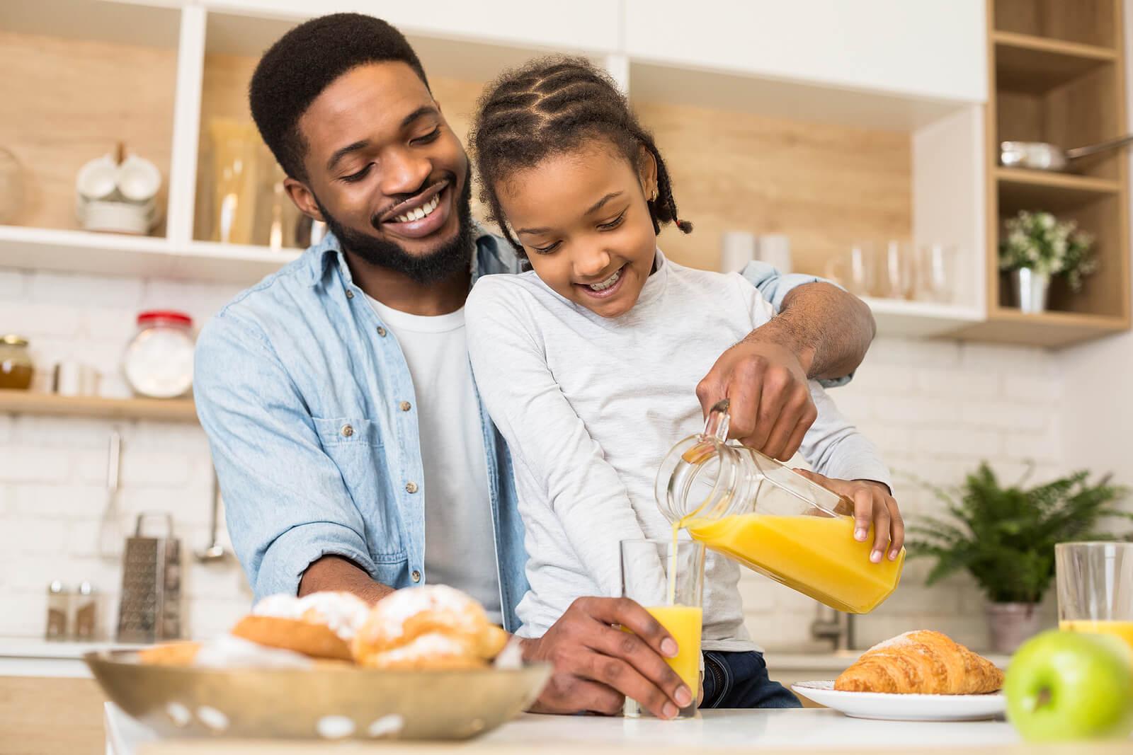 Padre desayunando con su hija pensando en las necesidades del hijo único.