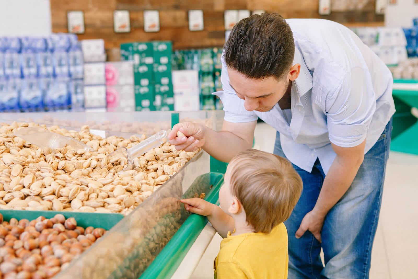 Padre con su hijo comprando frutos secos a granel.