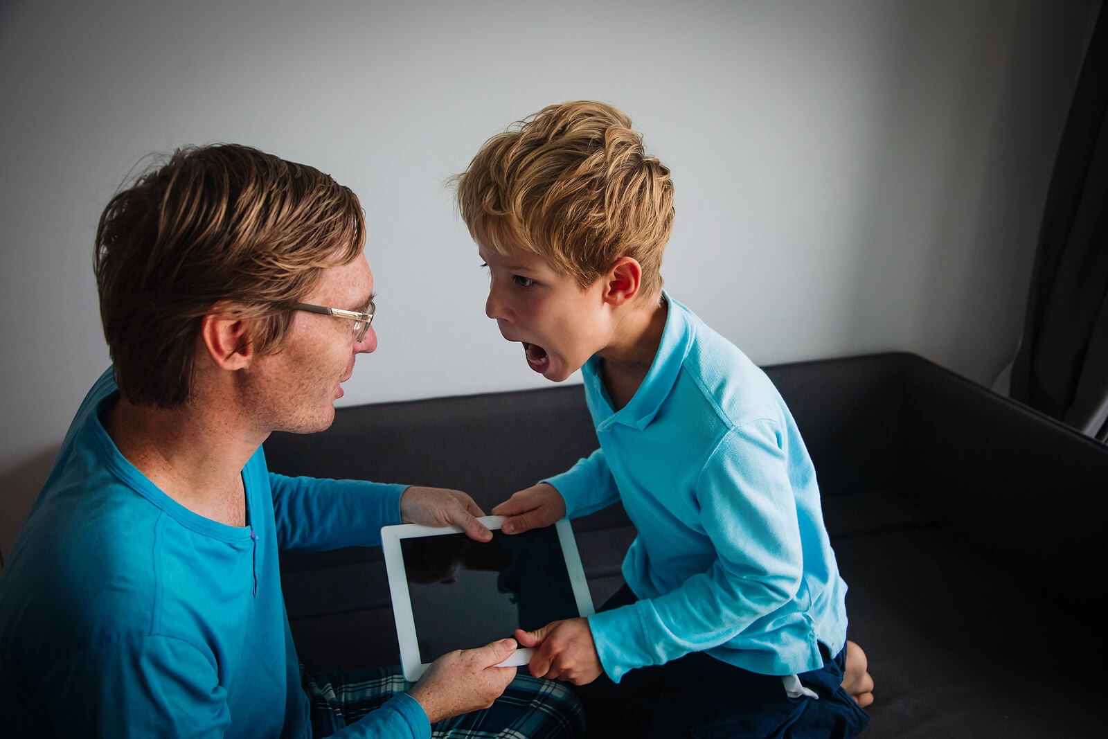 Padre e hija discutiendo por la tablet.