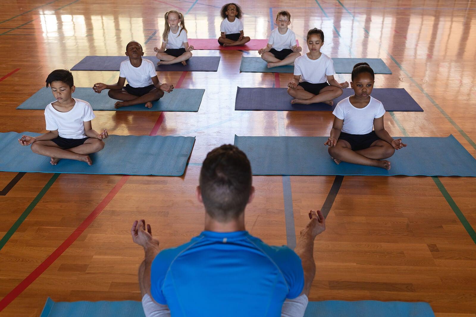 Profesor con sus alumnos haciendo yoga en el aula.