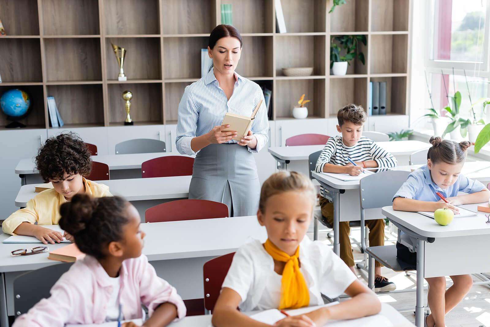Profesora en clase haciendo un dictado con sus alumnos para demostrar sus beneficios.