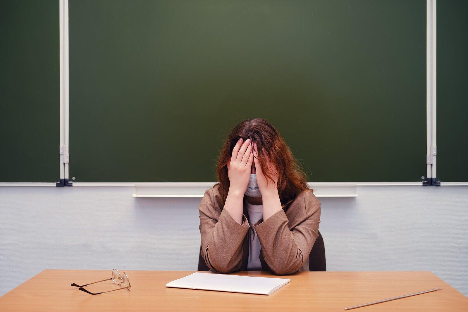 Profesora llorando en la mesa de clase porque sufre bullying.
