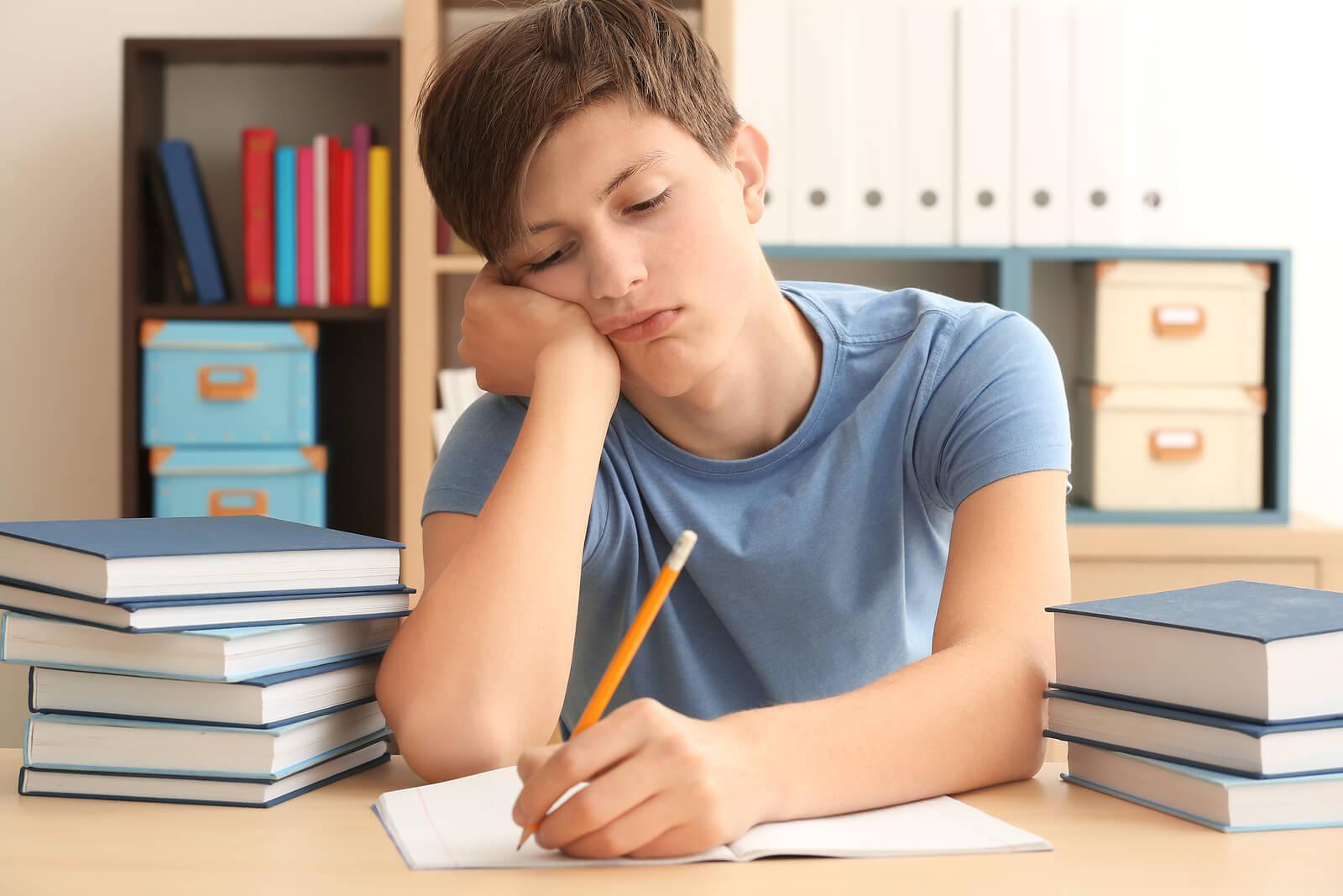 Adolescente haciendo deberes con apatía.