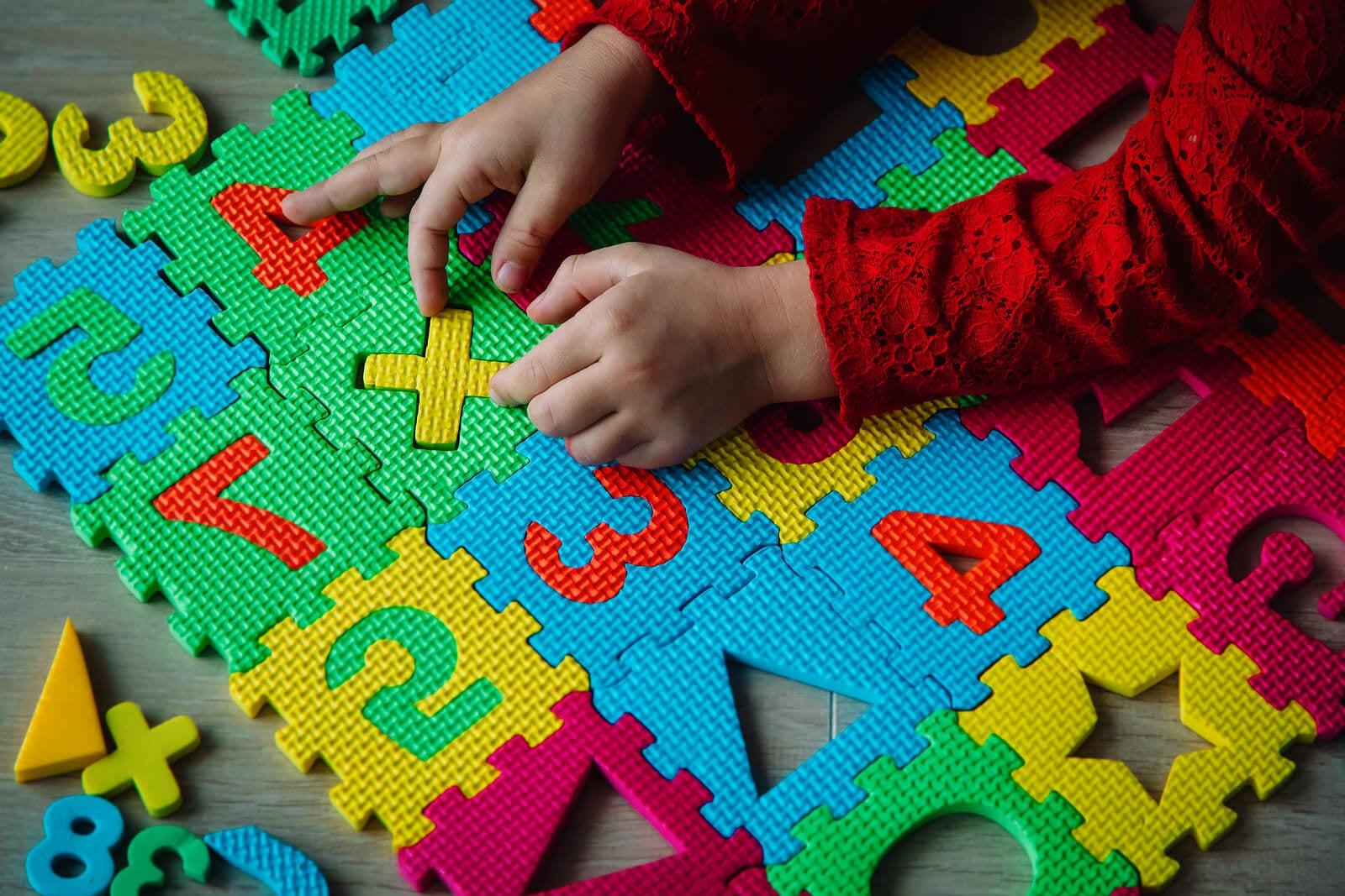 Niño jugando en una alfombra con números porque saber contar no implica conocerlos.