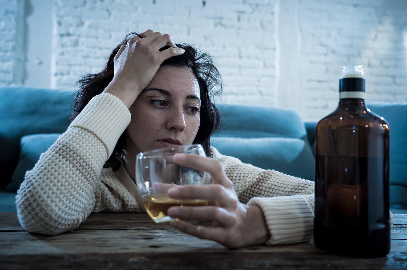 Mujer bebiendo alcohol sin parar; sufre alcoholismo materno.