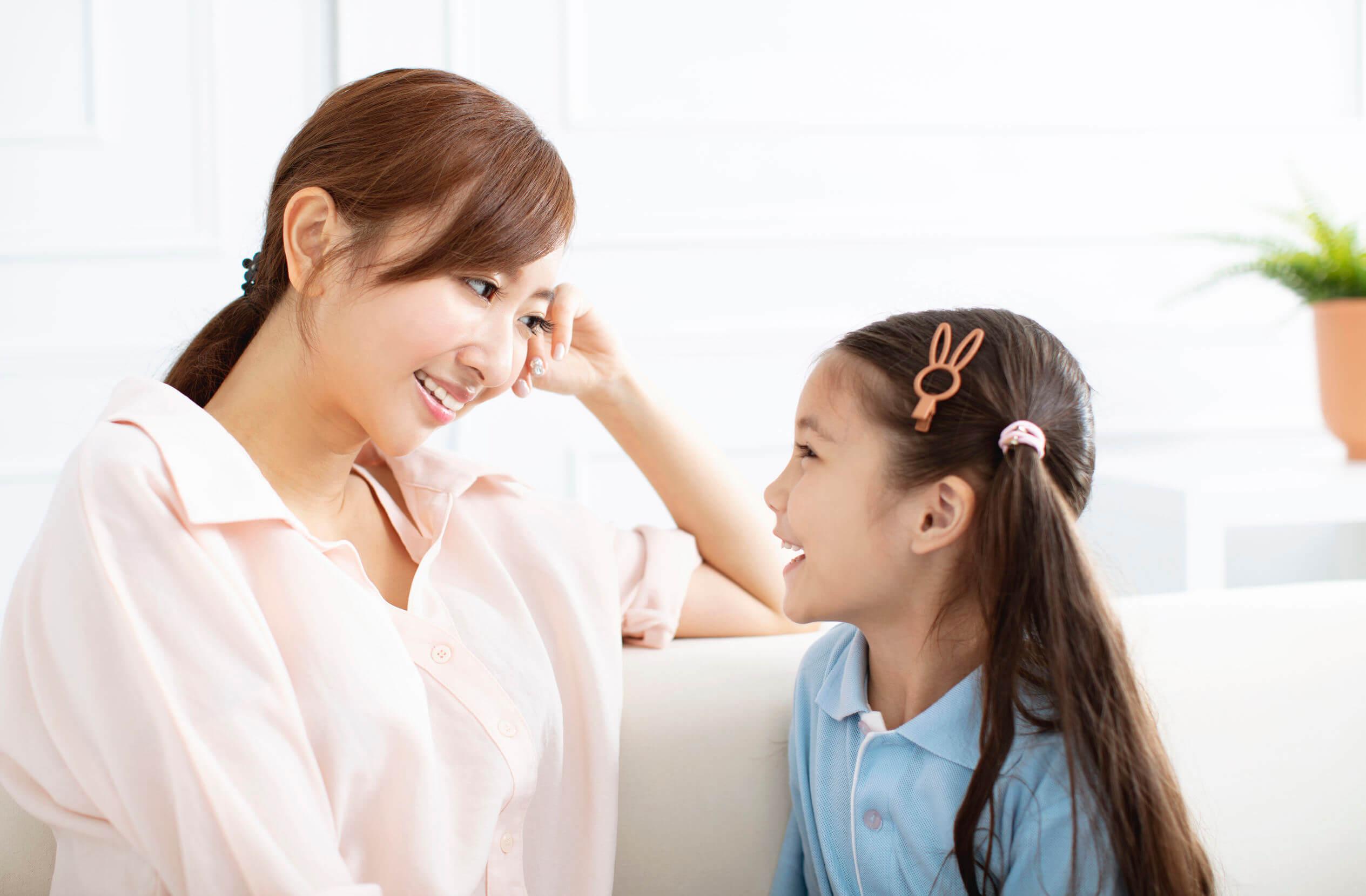 Madre hablando con su hija para estimular la memoria infantil.