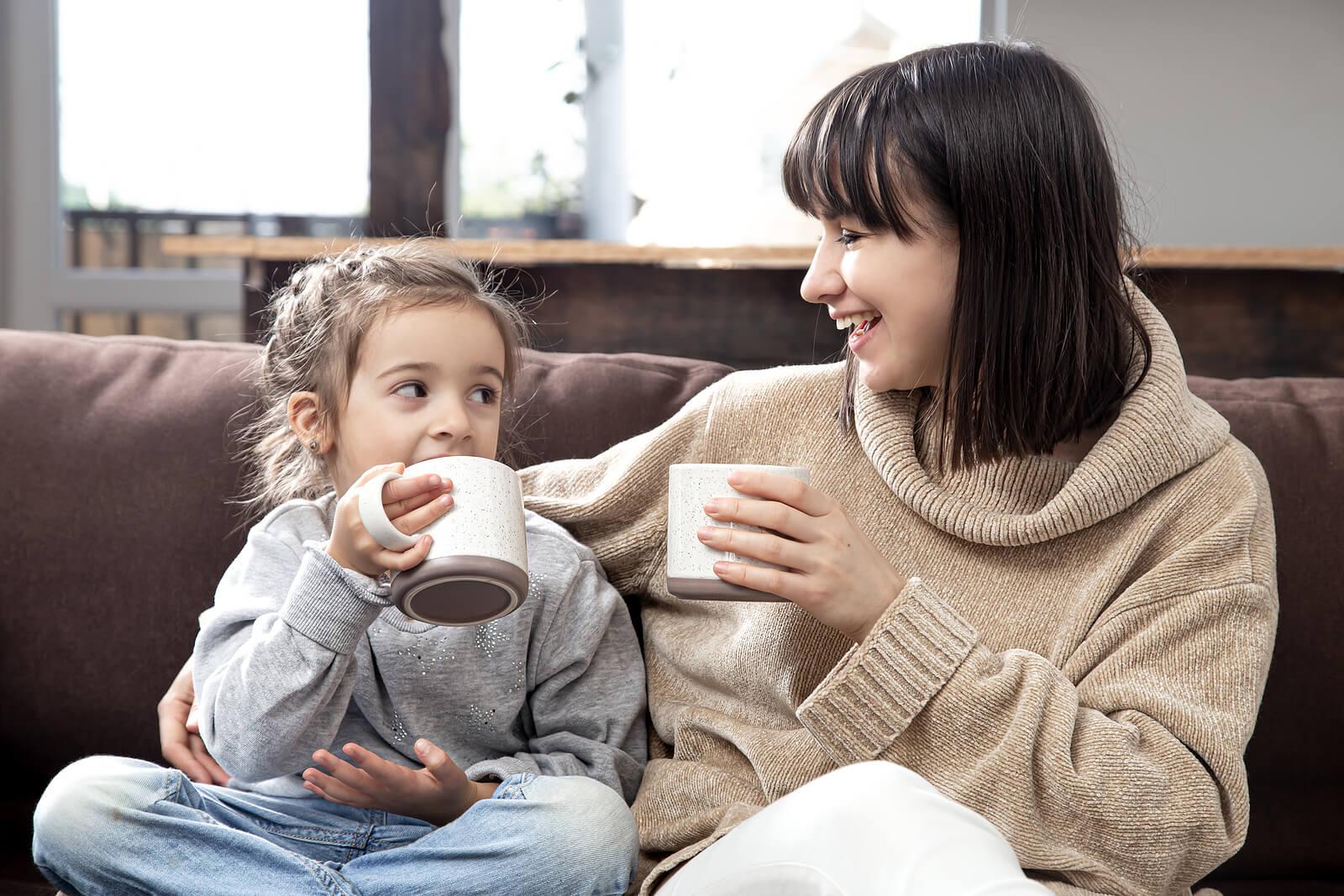 Madre hablando con su hija sobre cómo le ha ido el cole mientras beben chocolate.