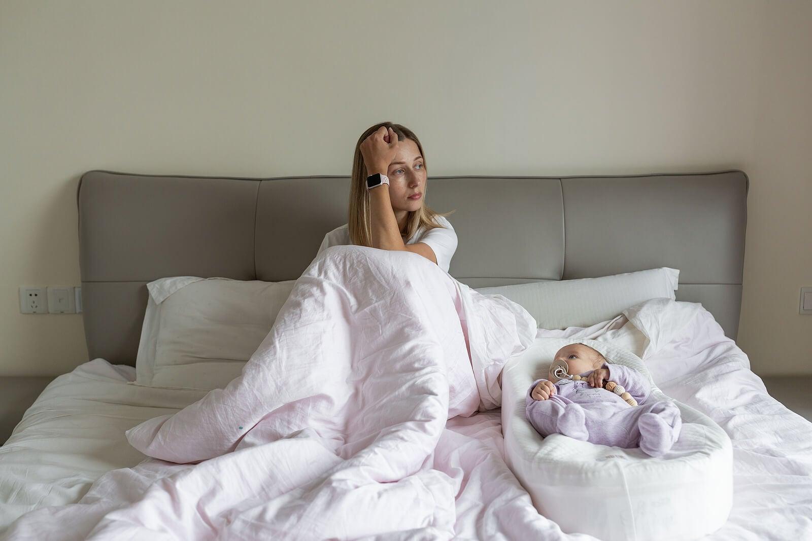 Madre llorando con su bebé al lado porque tiene depresión posparto.