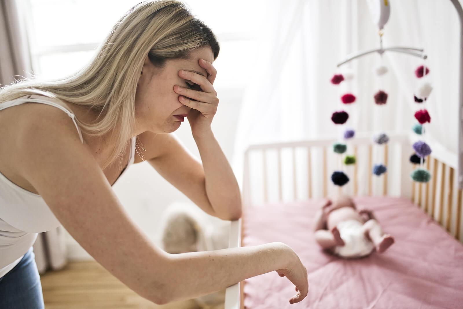 Madre llorando porque padece depresión posparto y rechazo hacia su hijo.