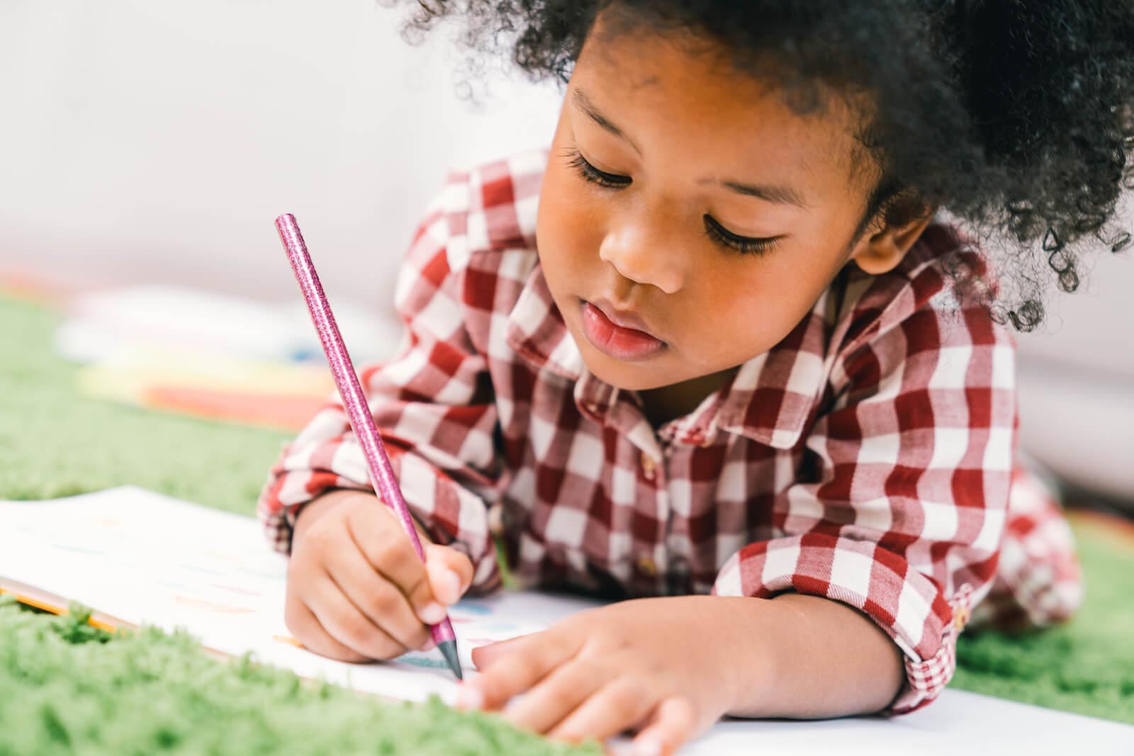 Niña muy inteligente escribiendo a temprana edad.