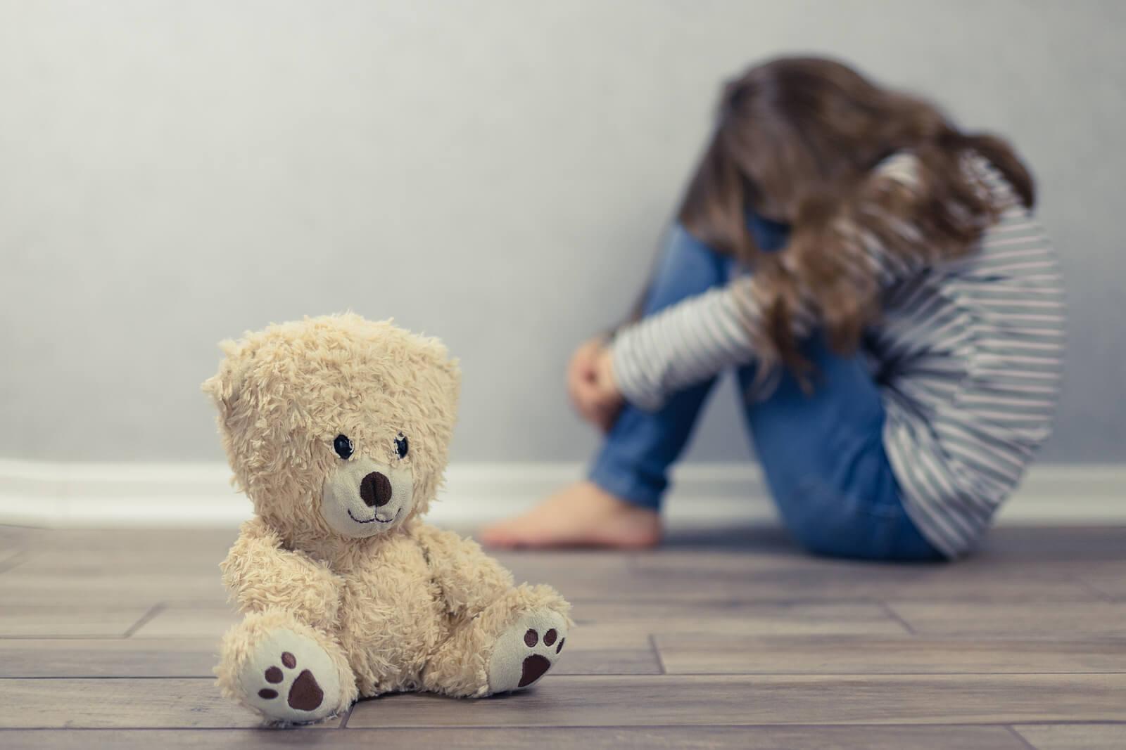 Niña muy triste con un oso de peluche mientras piensa en el suicidio.