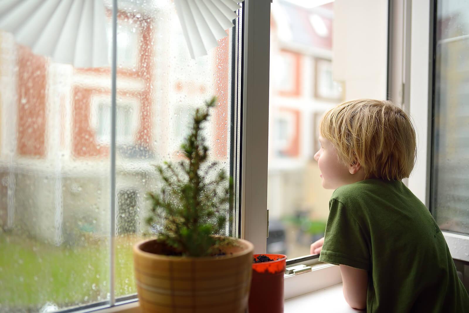 Niño aburrido mirando por la ventana.