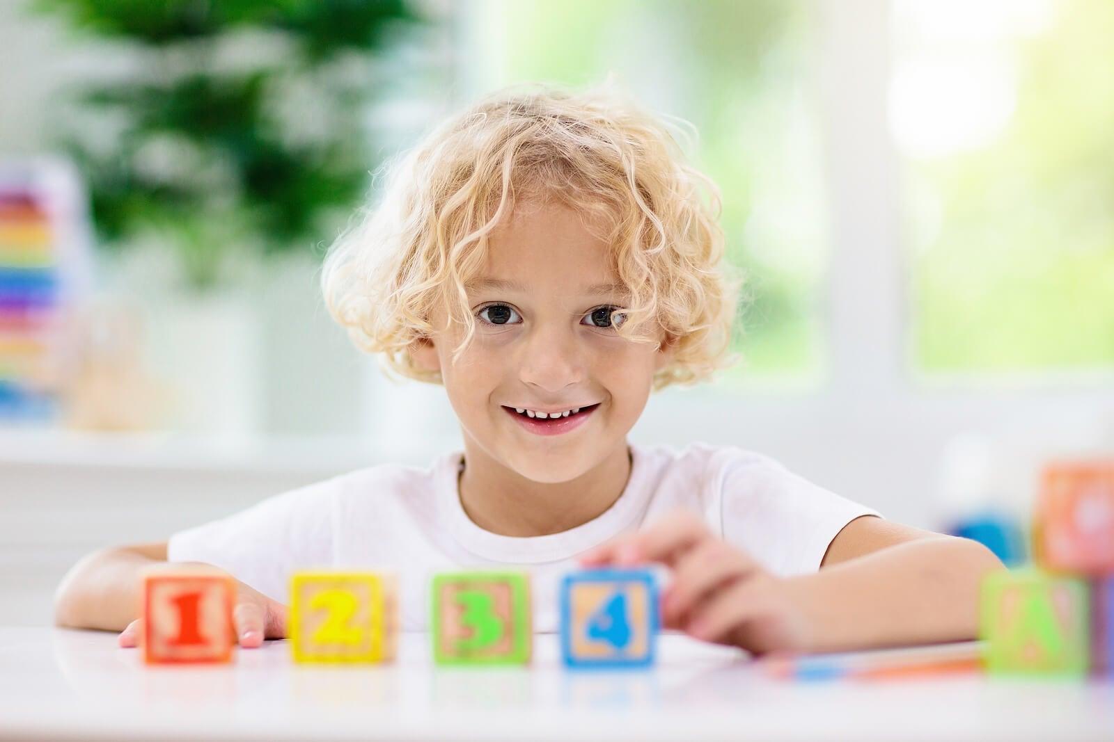 Niño con unos cubos de madera con números.