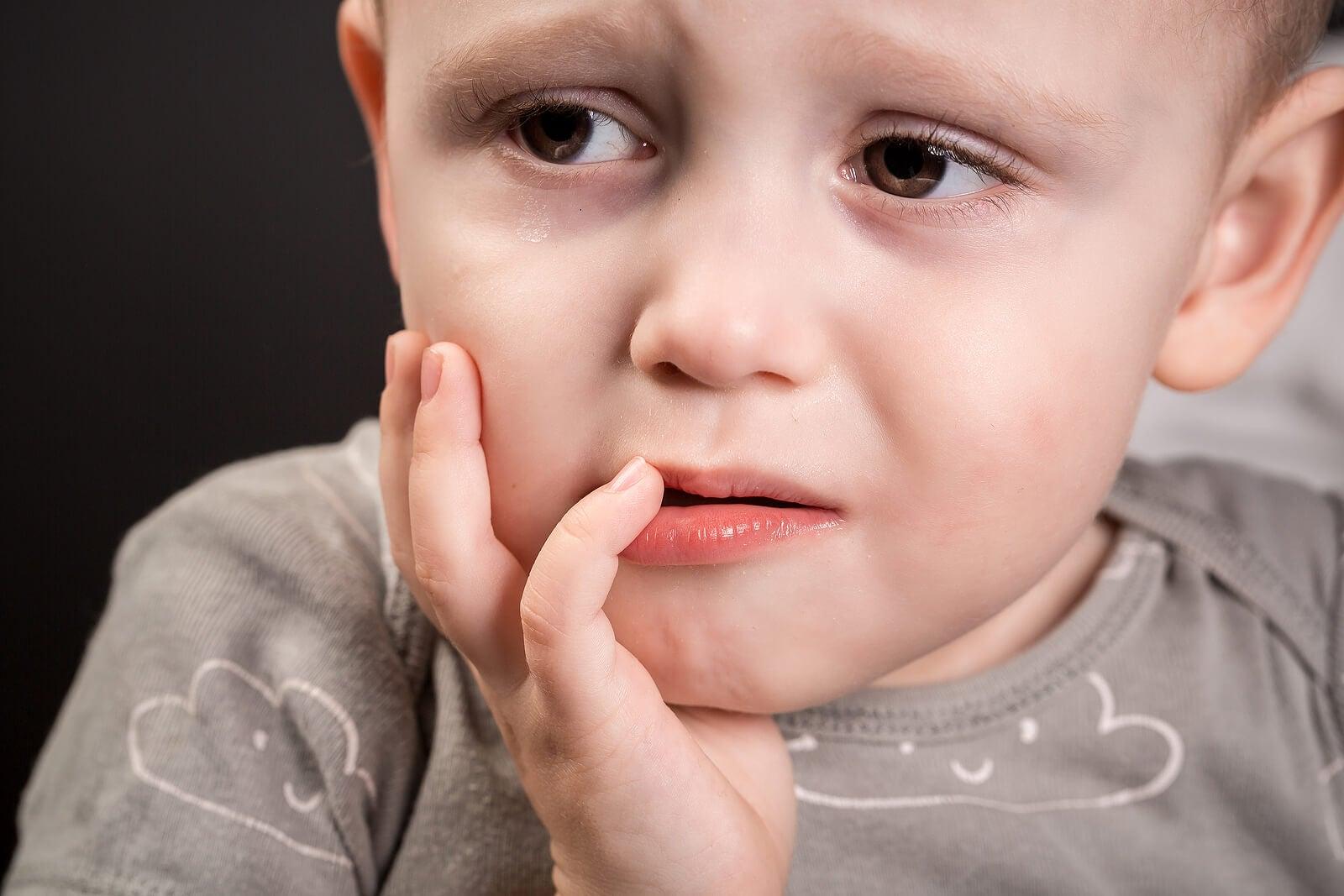 Niño con dolor en la boca y un diente negro.