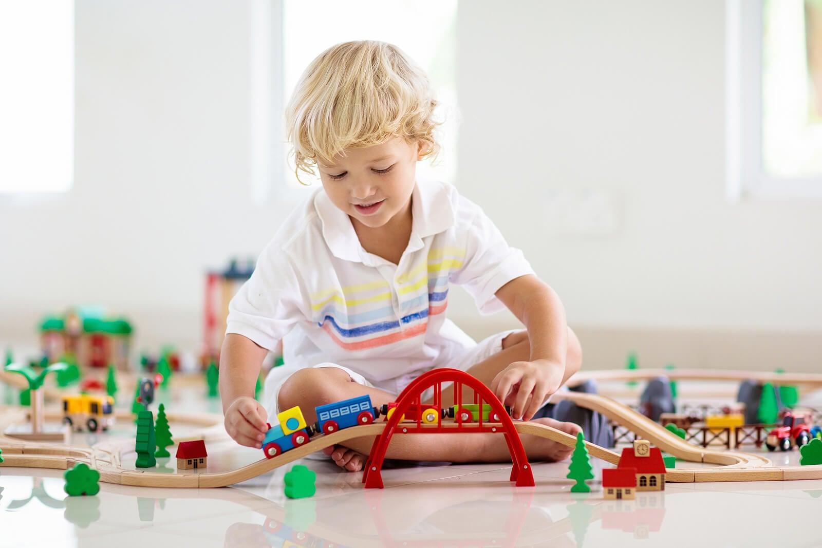 Niño jugando con trenes de madera.